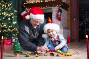 Father with his son play with model railway near christmas tree